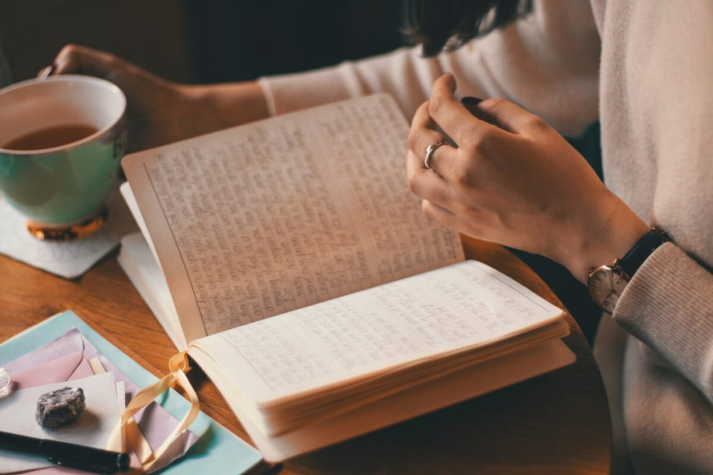 A torso of a person in a white long-sleeved top reading an open notebook with a cup of coffee