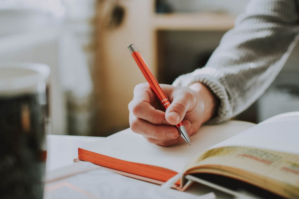 A hand holding an orange pen, poised above a page in an open notebook